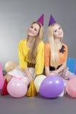 Adolescentes que se sientan con los globos coloridos Imagen de archivo