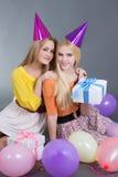 Adolescentes que se sientan con los regalos y los globos coloridos Imagen de archivo libre de regalías