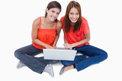 Adolescentes que se sientan con una computadora portátil en las piernas Imagen de archivo libre de regalías