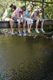 Adolescentes que se sientan en el puente de madera que mira abajo la corriente Fotografía de archivo libre de regalías