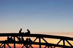 Adolescentes que se sientan en el puente en puesta del sol Imagen de archivo