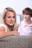Adolescentes que se sientan en el sofá Imagen de archivo libre de regalías