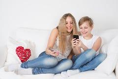 Adolescentes que se sientan en el sofá con el teléfono Imagen de archivo