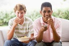 Adolescentes que se sientan en el sofá que come las patatas a la inglesa Fotos de archivo
