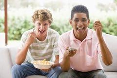Adolescentes que se sientan en el sofá que come las patatas a la inglesa Fotografía de archivo