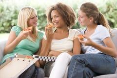 Adolescentes que se sientan en el sofá y que comen la pizza Imágenes de archivo libres de regalías