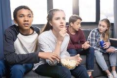 Adolescentes que se sientan en el sofá y que comen las palomitas del cuenco dentro Foto de archivo libre de regalías