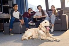Adolescentes que se sientan en el sofá y que miran el perro del golden retriever que miente en piso Foto de archivo