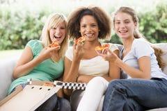Adolescentes que se sientan en el sofá y que comen la pizza Imagenes de archivo