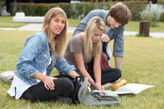 Adolescentes que se sientan en hierba Fotos de archivo libres de regalías