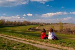 Adolescentes que se sientan en la hierba y hablar Imagen de archivo