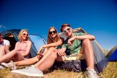 Adolescentes que se sientan en la tierra delante de las tiendas Imagenes de archivo