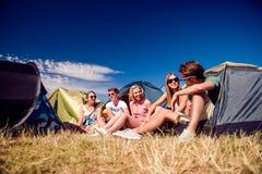 Adolescentes que se sientan en la tierra delante de las tiendas Foto de archivo