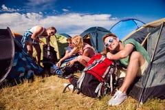 Adolescentes que se sientan en la tierra delante de las tiendas Imagen de archivo libre de regalías