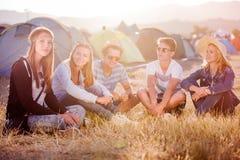 Adolescentes que se sientan en la tierra delante de las tiendas Fotografía de archivo libre de regalías
