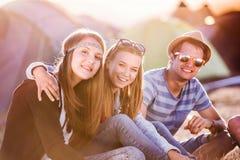 Adolescentes que se sientan en la tierra delante de las tiendas Imagen de archivo