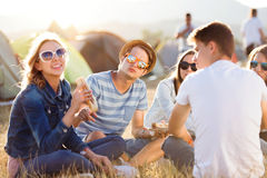 Adolescentes que se sientan en la tierra delante de las tiendas, comiendo Imágenes de archivo libres de regalías