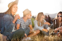 Adolescentes que se sientan en la tierra delante de las tiendas, comiendo Foto de archivo libre de regalías