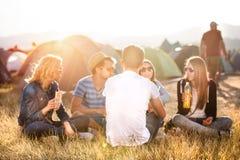Adolescentes que se sientan en la tierra delante de las tiendas, comiendo Imagen de archivo