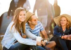 Adolescentes que se sientan en la tierra delante de las tiendas, descansando Imágenes de archivo libres de regalías
