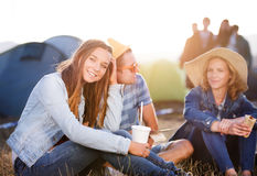 Adolescentes que se sientan en la tierra delante de las tiendas, descansando Fotografía de archivo libre de regalías