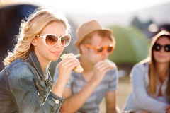 Adolescentes que se sientan en la tierra delante de las tiendas y de la consumición Imagen de archivo