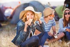 Adolescentes que se sientan en la tierra delante de las tiendas y de la consumición Imágenes de archivo libres de regalías