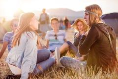 Adolescentes que se sientan en la tierra, hablando, divirtiéndose Fotos de archivo