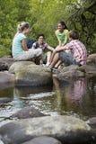Adolescentes que se sientan en piedras por el río en bosque Foto de archivo libre de regalías