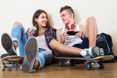 Adolescentes que se sientan en piso con los teléfonos móviles Imagenes de archivo
