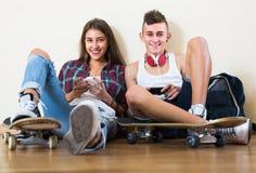 Adolescentes que se sientan en piso con los teléfonos móviles Imagen de archivo