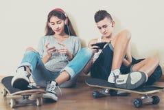 Adolescentes que se sientan en piso con los teléfonos móviles Foto de archivo