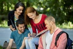 Adolescentes que se sientan en un banco y que hacen la preparación Foto de archivo