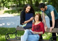 Adolescentes que se sientan en un banco y que hacen la preparación Fotografía de archivo