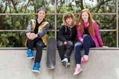 Adolescentes que se sientan en un halfpipe Foto de archivo libre de regalías