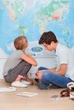 Adolescentes que se sientan por el mapa en sala de clase Imágenes de archivo libres de regalías