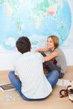 Adolescentes que se sientan por el mapa en sala de clase Imagen de archivo libre de regalías