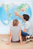 Adolescentes que se sientan por el mapa en sala de clase Foto de archivo