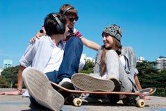 Adolescentes que se sientan por una calle Foto de archivo libre de regalías