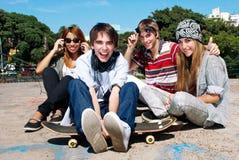 Adolescentes que se sientan por una calle Foto de archivo