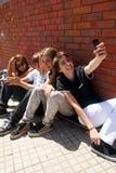 Adolescentes que se sientan por una calle Imagenes de archivo