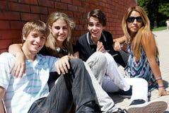 Adolescentes que se sientan por una calle Imagen de archivo