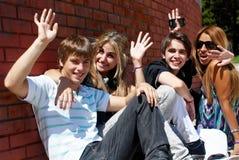 Adolescentes que se sientan por una calle Imágenes de archivo libres de regalías