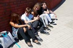 Adolescentes que se sientan por una calle Fotografía de archivo