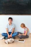 Adolescentes que se sientan por una pizarra en sala de clase Fotos de archivo libres de regalías