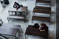 Adolescentes que se sientan solo en una cantina vacía Imagen de archivo libre de regalías