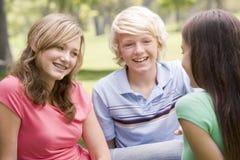 Adolescentes que se sientan y que conversan Foto de archivo libre de regalías