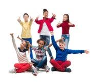 Adolescentes que se sientan y que se colocan con los pulgares para arriba Fotos de archivo libres de regalías