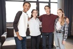 Adolescentes que se unen y que sonríen en la cámara dentro, adolescentes que tienen concepto de la diversión Foto de archivo libre de regalías