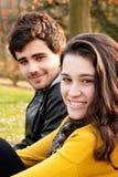 Adolescentes que sentam-se na grama Fotos de Stock